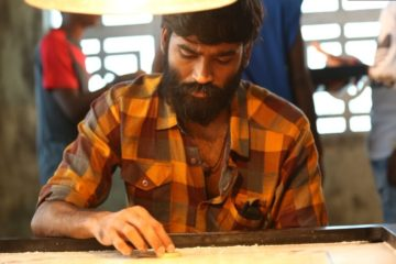 Dhanush as Anbu playing Carrom board in Vada Chennai