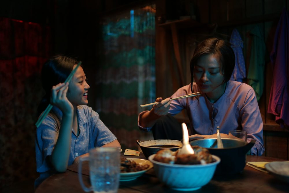 Veronica Ngo eating meal with her daughter in Vietnamese film Furie