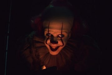 Pennywise played by Bill Skarsgård smiling in the clown dress up for the Second Chapter of IT Trailer