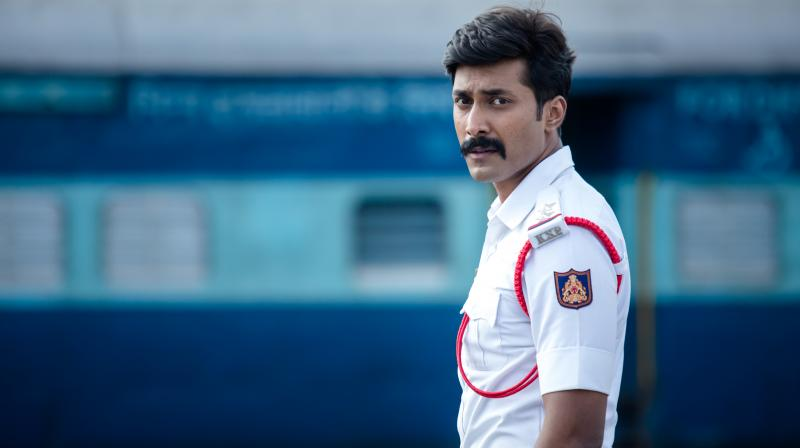 Rishi wearing Traffic cop dress in front of a train in Kavaludaari film, dir. Hemanth Rao