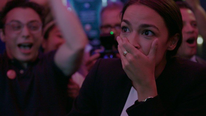 Alexandria Ocasio-Cortez standing in a bar and looking surprised as she won the Primary - Netflix Original Movies of 2019