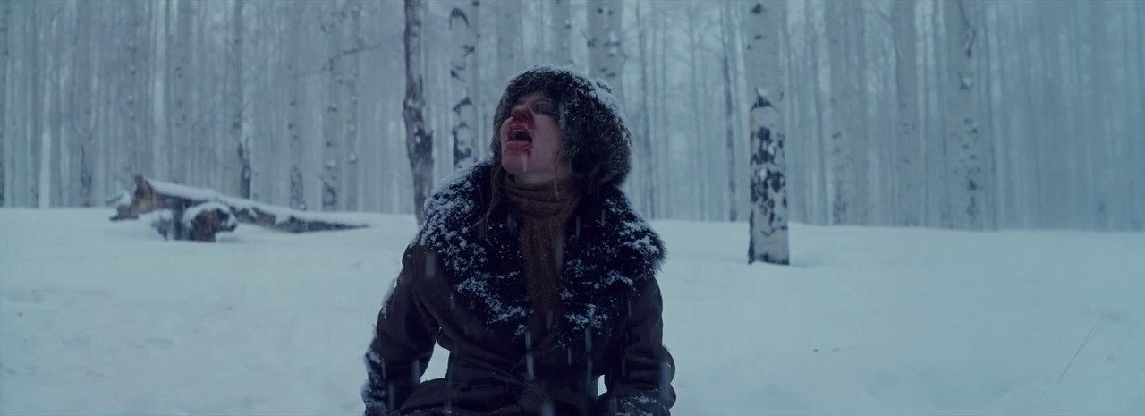 Jennifer Jason Leigh in Quentin Tarantino's The Hateful Eight that releases on Netflix as a miniseries. She is tasting water from her bloodied mouth sitting in the middle of a snowy mountain.