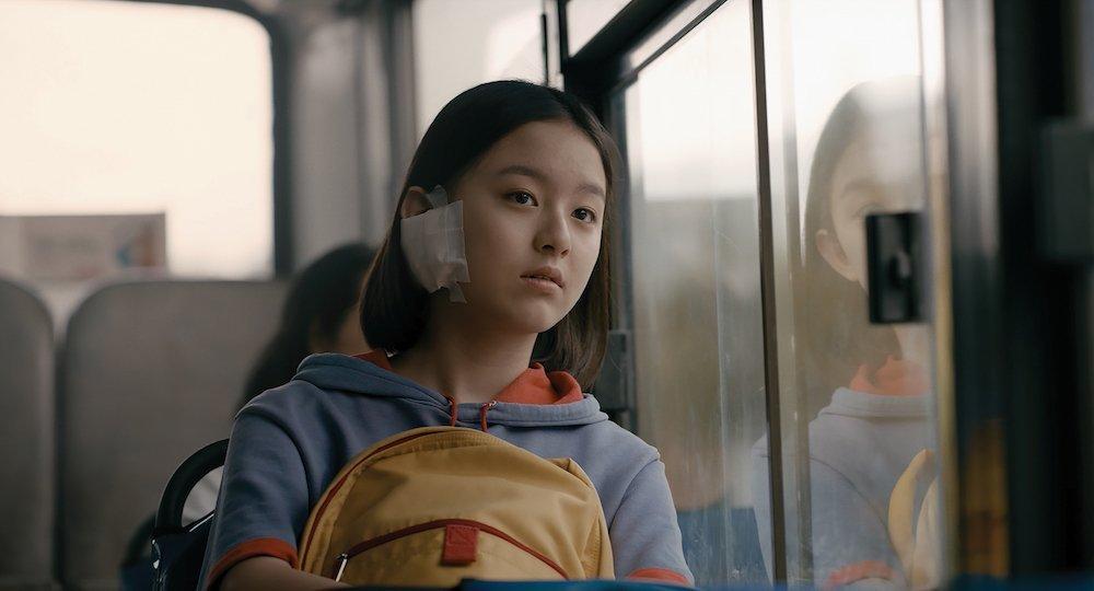 Eunhee (Ji-hu Park) sitting in bus, holding her school bag in House of Hummingbird