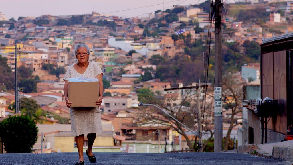 A woman carrying a box in 'In the Heart of the World'